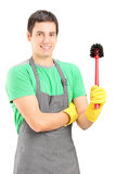 拿着洗手间笤帚的一微笑的男性擦净人 免版税库存图片