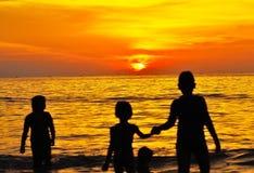 与幼儿的日落海滩 免版税库存照片