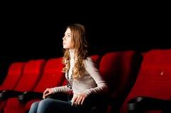 Νέα ελκυστική συνεδρίαση γυναικών σε έναν κινηματογράφο Στοκ εικόνες με δικαίωμα ελεύθερης χρήσης