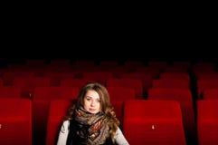 Νέα ελκυστική συνεδρίαση γυναικών σε έναν κινηματογράφο Στοκ φωτογραφία με δικαίωμα ελεύθερης χρήσης