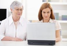 美丽的妇女和有膝上型计算机的高级母亲 免版税图库摄影