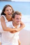 扛在肩上在海滩的愉快的夫妇。 免版税库存图片