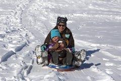 母亲和子项获得乐趣下滑在雪撬小山下 图库摄影