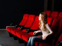 Νέα ελκυστική συνεδρίαση γυναικών σε έναν κινηματογράφο Στοκ Εικόνα