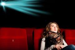 Νέα ελκυστική συνεδρίαση γυναικών σε έναν κινηματογράφο Στοκ Φωτογραφία