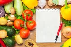 在木背景和笔记本的有机蔬菜 免版税库存照片