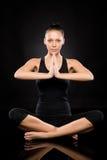执行瑜伽的妇女坐楼层 免版税库存照片