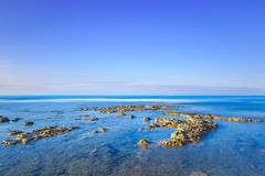 岩石在蓝色海洋在日出的清楚的天空下。 免版税库存图片