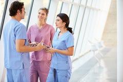 医疗人员联系在有数字式片剂的医院走廊 免版税库存照片