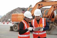 建筑工人和挖掘机 免版税库存图片