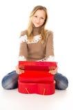 坐在礼物盒附近的青少年的女孩 免版税图库摄影