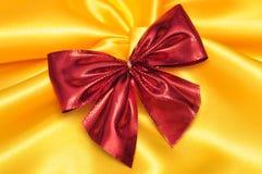 在黄色缎的红色弓 免版税库存照片