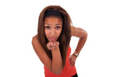 Ευτυχής αφροαμερικανίδα νέα γυναίκα που απομονώνεται στο λευκό που φυσά ένα φιλί Στοκ Φωτογραφίες