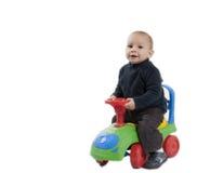 乘坐他的玩具汽车的男孩 免版税库存照片