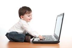 Περιστασιακό μωρό που χαμογελά ενώ παίζει με έναν φορητό προσωπικό υπολογιστή Στοκ Φωτογραφία