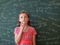 有数学公式的女小学生和黑板 免版税图库摄影