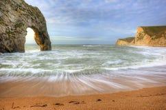 在海洋的充满活力的日出有在前景的岩石栈的 免版税库存图片