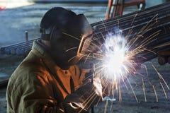 Συγκόλληση εργαζομένων με το ηλεκτρόδιο ηλεκτρικών τόξων Στοκ Φωτογραφίες