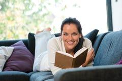 微笑的妇女休息的读取沙发了解国内 库存图片