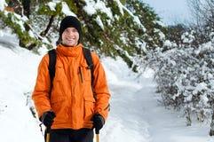 突出在雪森林里的远足者 库存图片