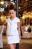 皮革诉讼的女孩在装饰路灯柱附近突出 免版税库存照片