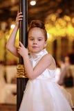 倾斜对路灯柱的小女孩立场 免版税库存照片