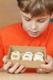 男孩看看开放箱皱纸板用曲奇饼 免版税图库摄影