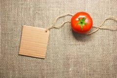 蕃茄蔬菜和在袋装的背景纹理的价牌 免版税库存照片