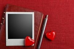 Немедленные рамка и сердца фото фильма на красной мешковине Стоковая Фотография
