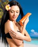 Женщина в бикини прикладывая сливк блока солнца на теле Стоковое фото RF
