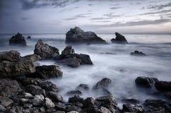 黑暗的海滩岩石 免版税图库摄影