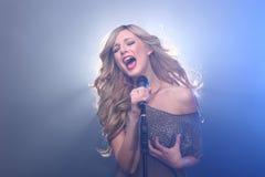 在阶段唱歌的美丽的白肤金发的摇滚明星 免版税库存照片