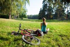 女孩骑自行车者放松春天公园的正面图全景 免版税库存图片