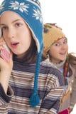 美丽的女孩在温暖的冬天给发表演讲关于移动电话穿衣 免版税库存照片