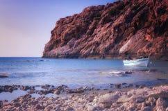 在小船和岩石陆岬的日落 免版税库存图片