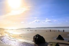 在日落的通知破碎机在一个金黄多岩石的海滩 库存照片