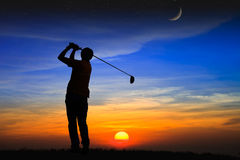 现出轮廓高尔夫球运动员在日落 库存照片