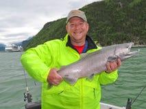 阿拉斯加-拿着大马哈鱼的愉快的人 免版税库存照片