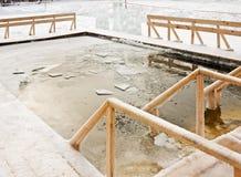 在冰的漏洞在突然显现沐浴的冬天森林 免版税图库摄影