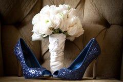 蓝色婚礼穿上鞋子白色玫瑰花束 免版税图库摄影