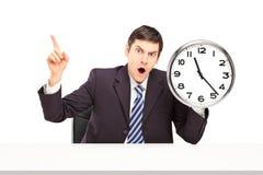 坐和拿着壁钟的恼怒的生意人 免版税库存照片