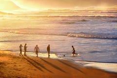 踢在海滩的人们足球 免版税库存图片