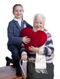 有拿着重点枕头的孙女的祖母 免版税图库摄影
