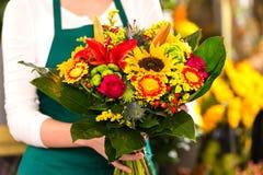 拿着花束五颜六色的花店的卖花人辅助 免版税图库摄影