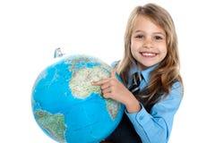 暂挂地球和指向的俏丽的小学生 库存照片