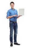 拿着膝上型计算机的年轻人 免版税库存照片