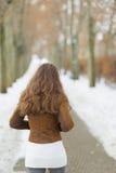 走在冬天公园的少妇。 背面图 免版税库存图片