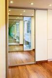 下滑门在现代大厅内部的镜子衣橱 免版税库存照片