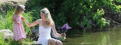 在湖照顾和她的小女儿 免版税库存图片