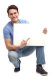 指向空白董事会的年轻人 免版税库存图片